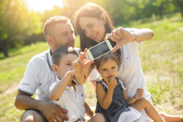 Cheerful family making selfie. Parents having fun with their kids outdoors. Cute family having picnic.