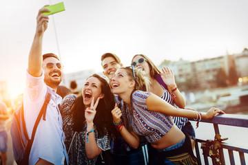 Happy young friends taking selfie on street