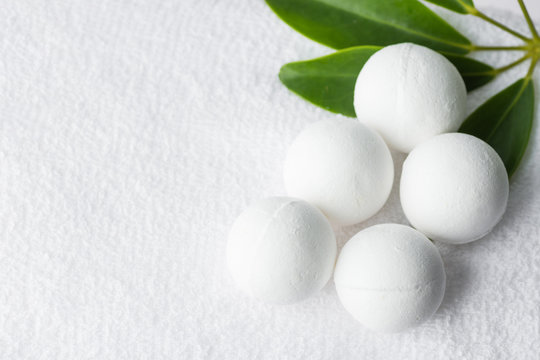 Handmade salt bath bombs in balls shape from organic vegan natural ingredients on white towel green house plants. Spa wellness body care well-being concept
