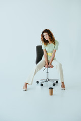 attractive redhead young woman sitting on black office chair near paper cup on grey