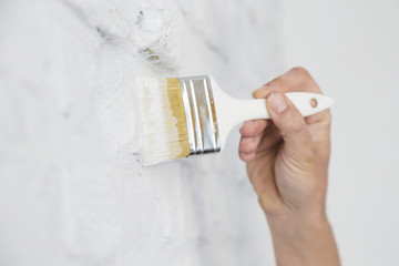 Painting a white brick wall with a paint brush