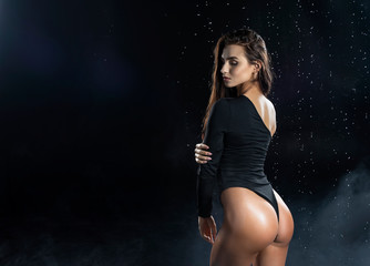 Beautiful leggy and booty athletic fitness girl model, wearing a black body, with wet oily skin, posing under water drops in theatrical smoke on a black background