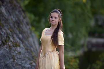 beautiful young princess brunette in a golden dress in the park