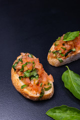 Delicious Italian antipasti bruschetta on black background. Close-up.