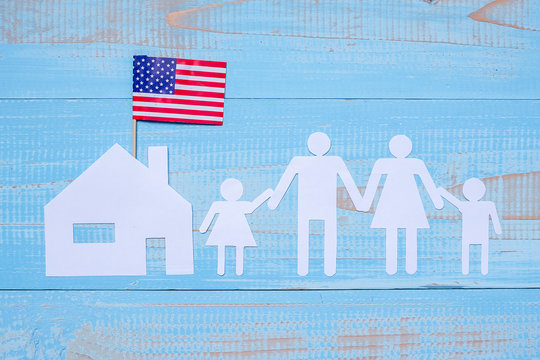 People or Family and home paper shape with  flag of the United States of America on blue wooden background. USA holiday of Veterans, Memorial, Independence and Labor Day