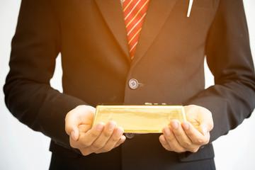 Businessman holding gold bar