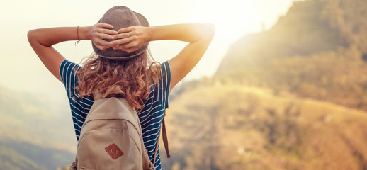Woman traveler hipster with backpack holding hat and looking forward at amazing mountains and valley view. Space for text. Fototapete