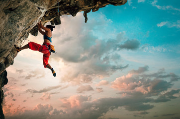 Athletic Woman climbing on overhanging cliff rock with sunrise sky background Wall mural