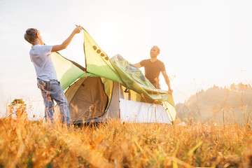 Father and son install tent for camping on sunny forest glade.Trekking with kids concept image