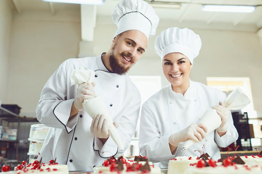 Confectioners with a bag for the cream will decorate the cake.