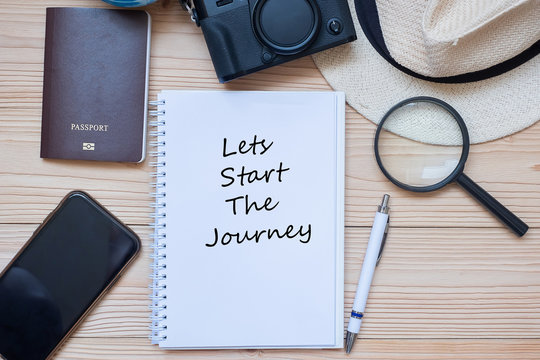 Lets start the joueney word on notebook with accessories, Camera, Passport, Magnifying, smart Phone and hat on wooden table, Top view. Travel planning concept