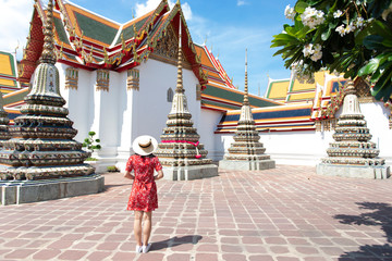 Wall Mural - Young Chinese or Asian woman is traveling and sightseeing inside Wat Pho temple in Bangkok, Thailand.