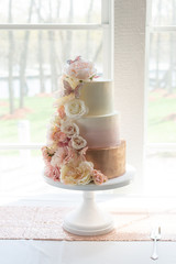Trendy 3 tier wedding cake with floral arrangment.