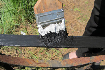 A black paint brush paints a rusty metal railing on a sunny day.