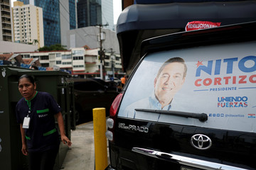 "A woman walks by a car with the picture of presidential candidate Laurentino ""Nito"" Cortizo, who was proclaimed the winner of the general election, in Panama City"