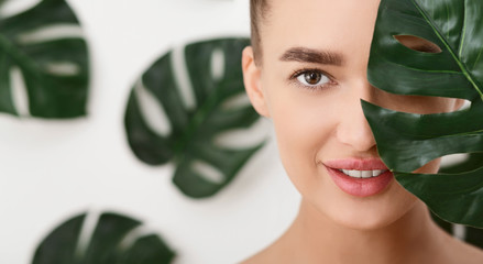 Young Woman With Perfect Skin Covering Half Of Face With Leaf