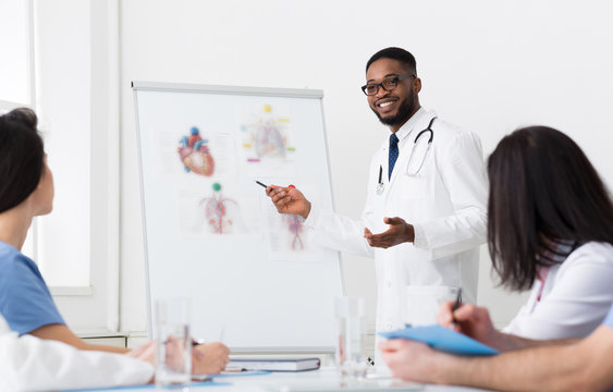 African Doctor Giving Lecture For Colleagues Using Whiteboard