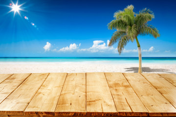 Desk of free space and summer background of ocean and beach with palm. Sunny day and blue sky.