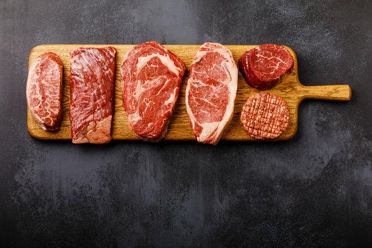 Variety of Raw Black Angus Prime meat steaks Top Blade, Machete, Rib Eye, Striploin, Tenderloin fillet Mignon, Cutlet Burger on wooden board on dark background