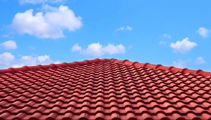 Obraz The old red tiles roof slope in pyramid shaped against white clouds and blue sky - fototapety do salonu