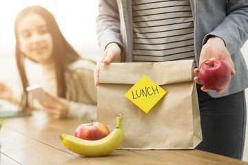 Mother Packing Healthy School Lunch For Daughter