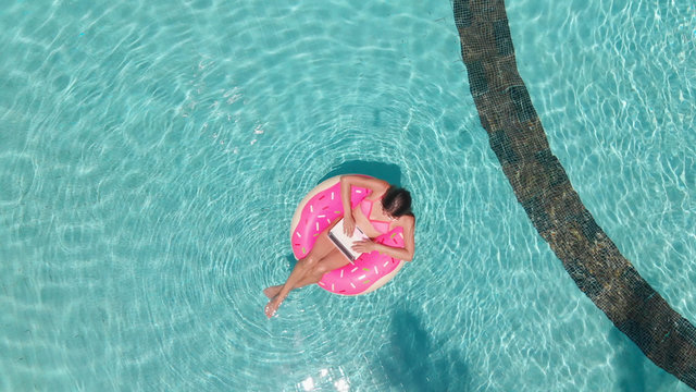 Young female freelancer sitting with a tablet in an inflatable circle in the pool. Aerial view