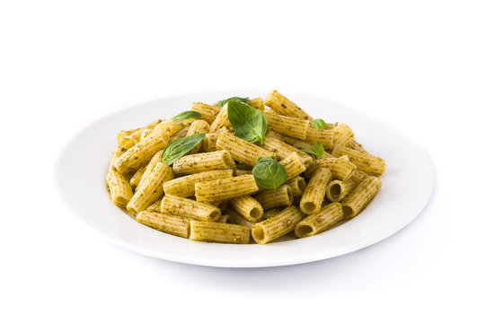 Penne pasta with pesto sauce and basil on a plate, isolated on white background
