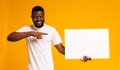 African-american man pointing at white blank board