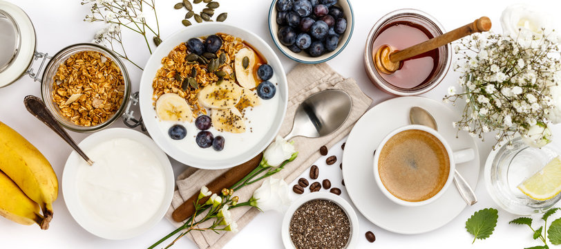 Oat granola with yogurt, honey, fresh bananas, blueberries, chia seeds in bowl  and cup of coffee on white background