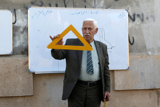 A retired Iraqi teacher who teaches his students for free, holds a triangle to explain mathematics in a street in Kirkuk