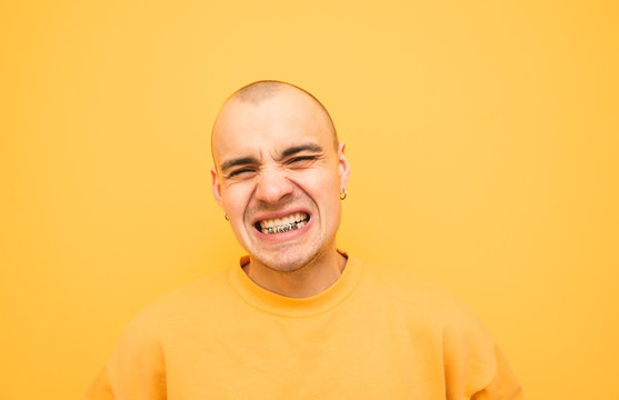 Expressive young man with a grillz on his teeth is angry with a yellow background wearing yellow clothes. Aggressive emotional guy is angry, isolated on a yellow background.