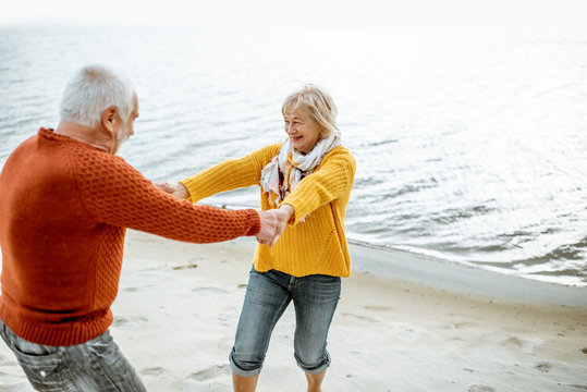 Lovely senior couple dressed in colorful sweaters dancing on the sandy beach, enjoying free time during retirement near the sea
