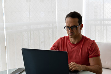 0f437b838 man working at his home office in pink shirt and glasses