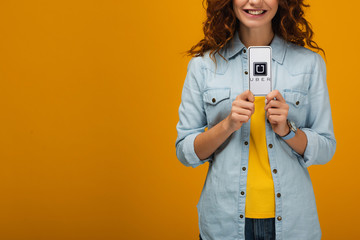 cropped view of cheerful curly woman holding smartphone with uber app on screen on orange
