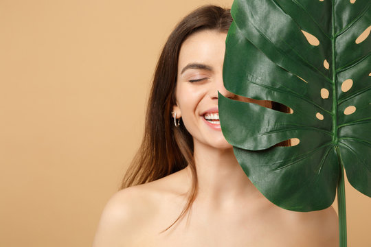 Close up brunette half naked woman 20s with perfect skin, nude make up palm leaf isolated on beige pastel wall background, studio portrait. Health care cosmetic procedures concept. Mock up copy space.