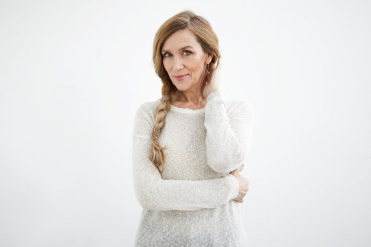 Elegance, beauty, modern lifestyle and maturity concept. Attractive elderly sixty year old woman with make up and long strong hair smiling happily, posing at blank white copyspace studio wall