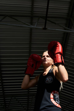 Female boxer in a muay thai training session.
