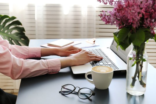 Feminine freelance workspace concept. Woman's hands typing on white laptopp with black keyboard, desk with matte blue table top. Freelance blogger writing an article. Close up, copy space for text.