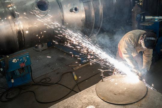 Male factory worker grinding on metal