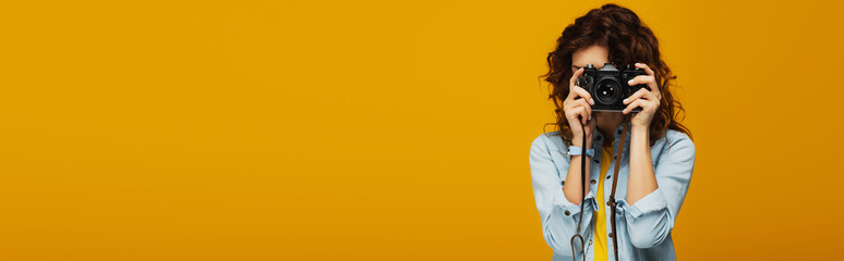 panoramic shot of curly redhead photographer covering face with digital camera isolated on orange