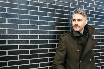 Fashionable businessman with bristle and grey hair looking away at black brick wall.