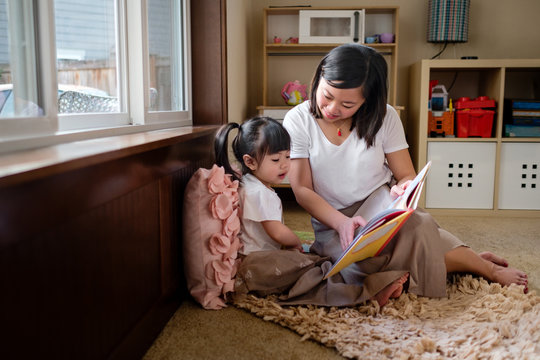 Asian Mother and Daughter Reading a Book at Home