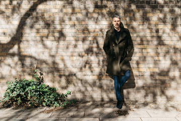Handsome man in khaki trench coat and jeans over brick wall.