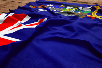 Flag of South Georgia And The South Sandwich Islands on a wooden desk background. Silk flag top view.