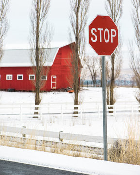 red stop sign on a road in front of a red barn in winter