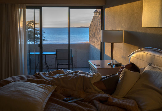 Man sitting in a hotel bed by himself - ocean view