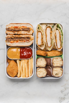 Unhealthy Bento box with junk food on white marble