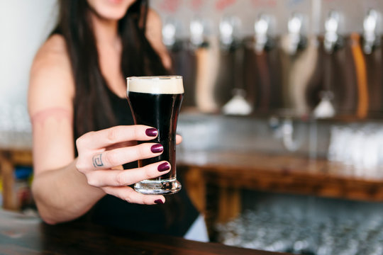 Woman's hand offering glass of beer