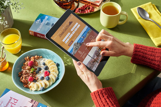 Woman searching for cheap flight via tablet at breakfast.