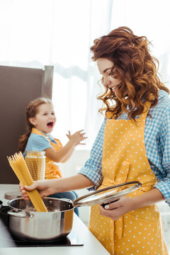 selective focus of mother in polka dot yellow apron putting raw spaghetti in pot while excited daughter laughing at background